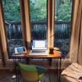 Photograph of small writing desk in front of tall windows, with a wet patio and lush trees beyond.